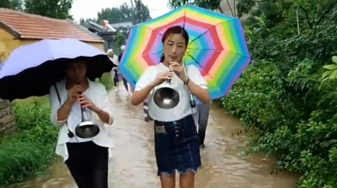下面流着水,上面打着伞,女唢呐手也坚持吹奏不停!